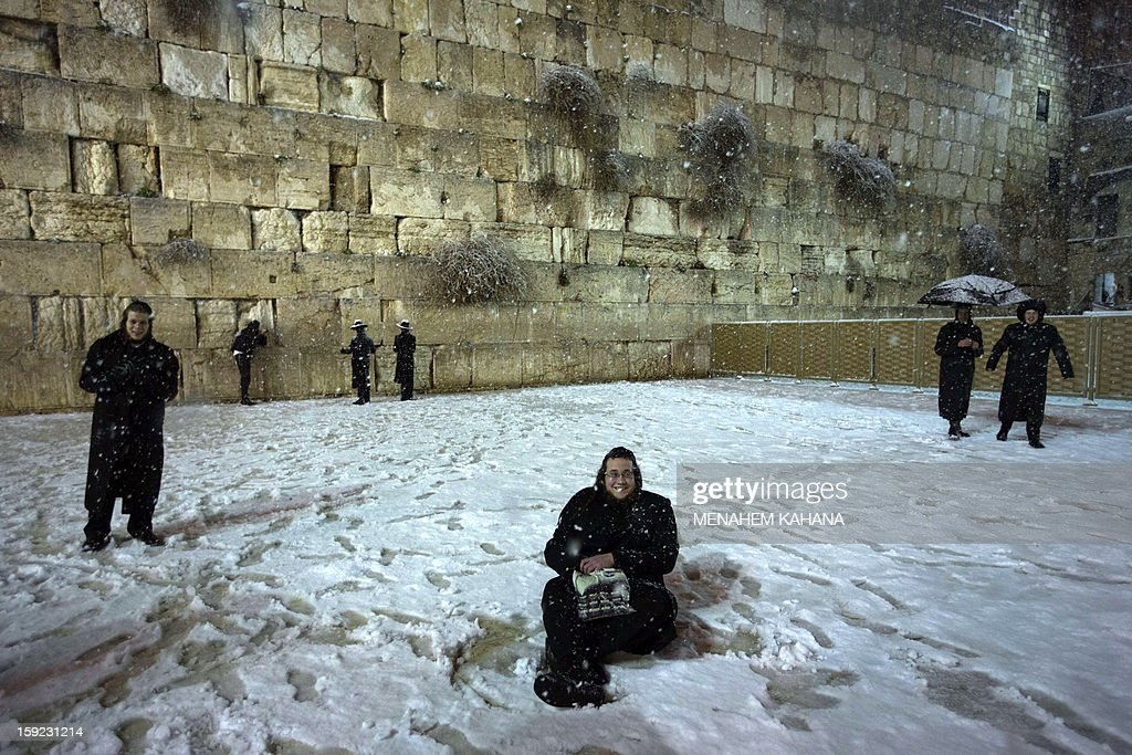 An Ultra-Orthodox Jewish man sits on the snow-covered ground at the Western Wall in the old city of Jerusalem on January 10, 2013. Jerusalem was transformed into a winter wonderland after heavy overnight snowfall turned the Holy City and much of the region white, bringing hordes of excited children onto the streets.