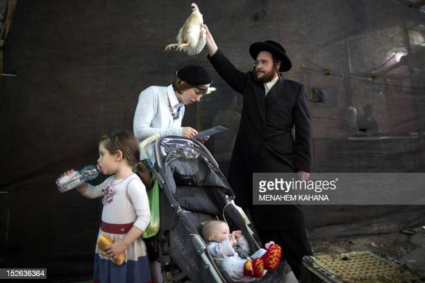 An UltraOrthodox Jewish man swings a chicken over his family during the Kaparot ceremony in the Mea Shearim neighbourhood of Jerusalem on September...