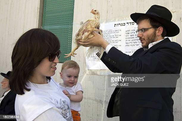 An UltraOrthodox Jewish man swings a chicken over the heads of members of his family during the Kaparot ceremony in the central Israeli city of Bnei...