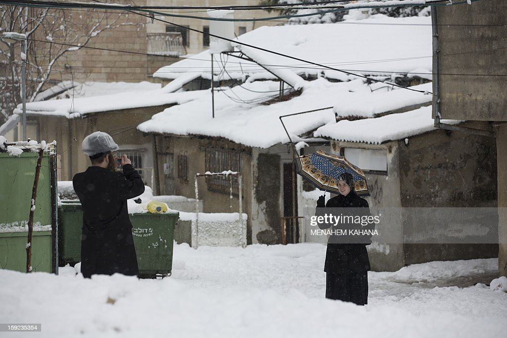 An Ultra-orthodox Jewish man takes a picture of a woman as snow falls in the Mea Shearim religious neighborhood of Jerusalem on January 10, 2013. Jerusalem was transformed into a winter wonderland after heavy overnight snowfall turned the Holy City and much of the region white, bringing hordes of excited children onto the streets.