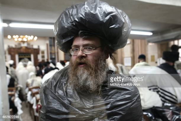 TOPSHOT An ultraOrthodox Jewish man wearing plastic above his clothes and hat is seen at a synagogue as worshippers read the book of Esther in...