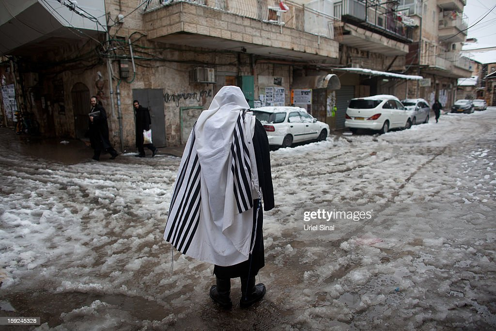 An Ultra-orthodox Jewish man wears a praying shawl in the snow in the Mea Shearim religious neighborhood on January 10, 2013 in Jerusalem, Israel.Ê