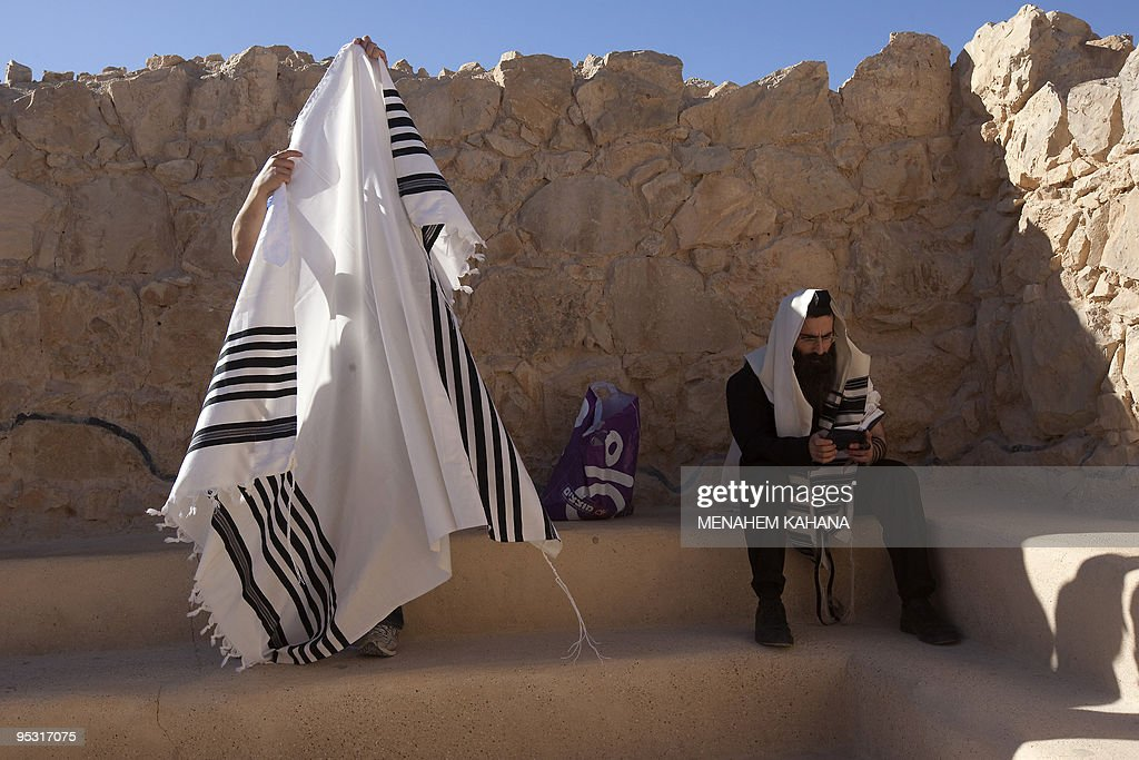 An ultra-Orthodox Jewish man wrapped in a talit, a prayer shawl, prays in the ancient synagogue of the hilltop fortress of Masada in the Judean desert on December 21, 2009. Masada, a ruined desert fortress steeped in myth, symbolism and controversy, is an archaeological site seen by many as an emblem of Israel's fighting spirit two millennia after 960 Jews are believed to have committed suicide on the isolated, wind-swept plateau rather than surrender to the Romans.