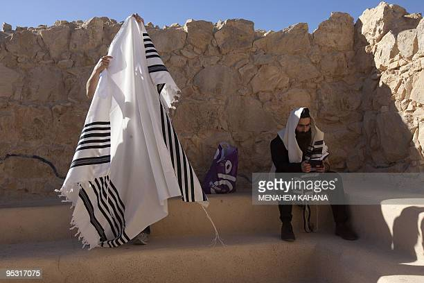 An ultraOrthodox Jewish man wrapped in a talit a prayer shawl prays in the ancient synagogue of the hilltop fortress of Masada in the Judean desert...