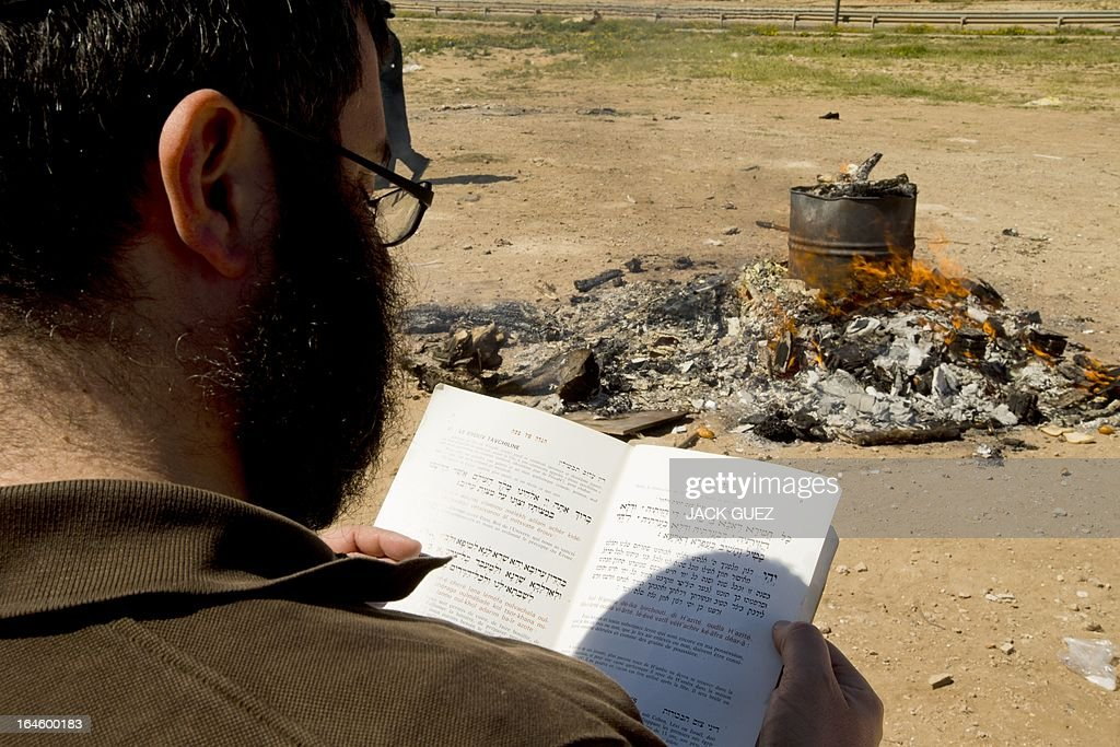 An Ultra-Orthodox Jewish prays as he watches leavened items burn in the final preparation before the start at sundown of the Jewish Passover holiday, in the Mediterranean coastal city of Netanya, central Israel, on March 25, 2013. All leavened food, such as bread, is forbidden to Jews during the week-long holiday, which to commemorate the Israelites' exodus from Egypt some 3,500 years ago. Due to the haste with which the Jews left Egypt, the bread they had prepared for the journey did not have time to rise. To commemorate their ancestors' plight, the religious avoid eating leavened food products throughout Passover. AFP PHOTO / JACK GUEZ