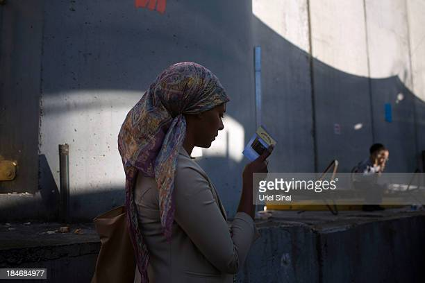 An ultraOrthodox Jewish woman prays under Israel's concrete seperation barrier which forms a heavilyguarded enclave protecting the tomb of the...
