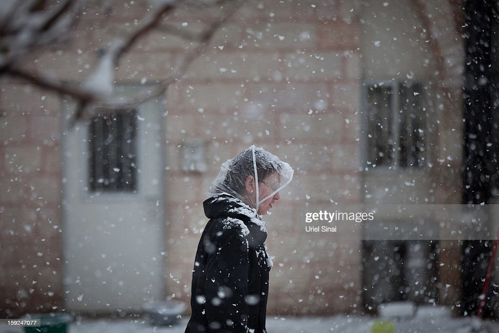 An Ultra-orthodox Jewish woman walks in the snow in the Mea Shearim religious neighborhood on January 10, 2013 in Jerusalem, Israel.
