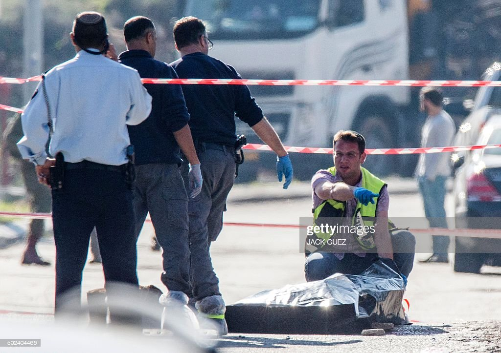 An UltraOrthodox Jewish Zaka volunteer covers the body of a Palestinian assailant who was shot dead after he stabbed two Israeli security guards at...
