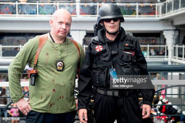 An Umbrella Corporation Guard cosplayer from the Resident Evil Franchise and a John McClane cosplayer seen during Day 1 of the London Super Comic Con...