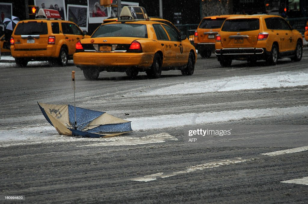 An umbrella lies on a street in New York on February 8, 2013 during a storm affecting the northeast US. The storm was forecast to bring the heaviest snow to the densely-populated northeast corridor so far this winter, threatening power and transport links for tens of millions of people and the major cities of Boston and New York. New York and other regional airports saw more than 4,500 cancellations ahead of what the National Weather Service called 'a major winter storm with blizzard conditions' along most of the region's coastline.
