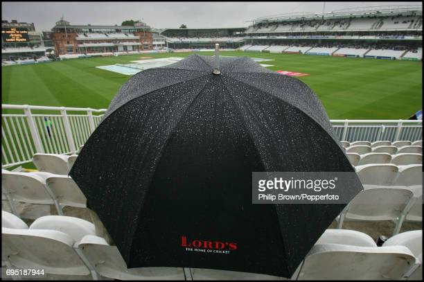 An umbrella with raindrops cascading down it as a fan waits for the cricket to start during the 1st Ashes Test match between England and Australia at...