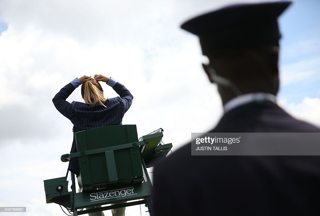 An umpire clips up her hair on the fourth day of the 2016 Wimbledon Championships at The All England Lawn Tennis Club in Wimbledon, southwest London, on June 30, 2016. / AFP / JUSTIN