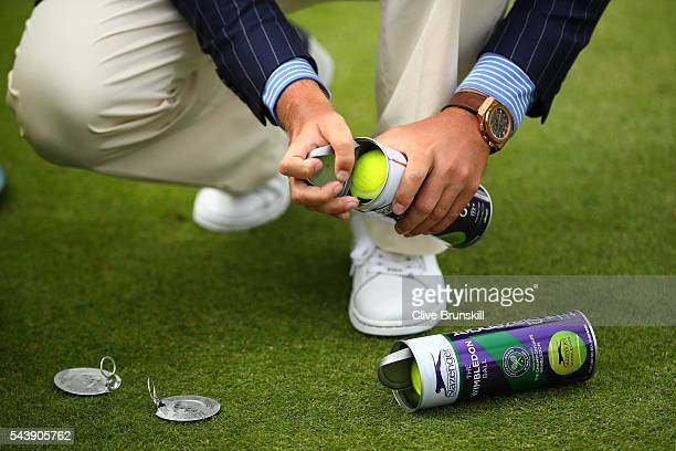 An umpire opens a new tin of tennis balls on day four of the Wimbledon Lawn Tennis Championships at the All England Lawn Tennis and Croquet Club on...