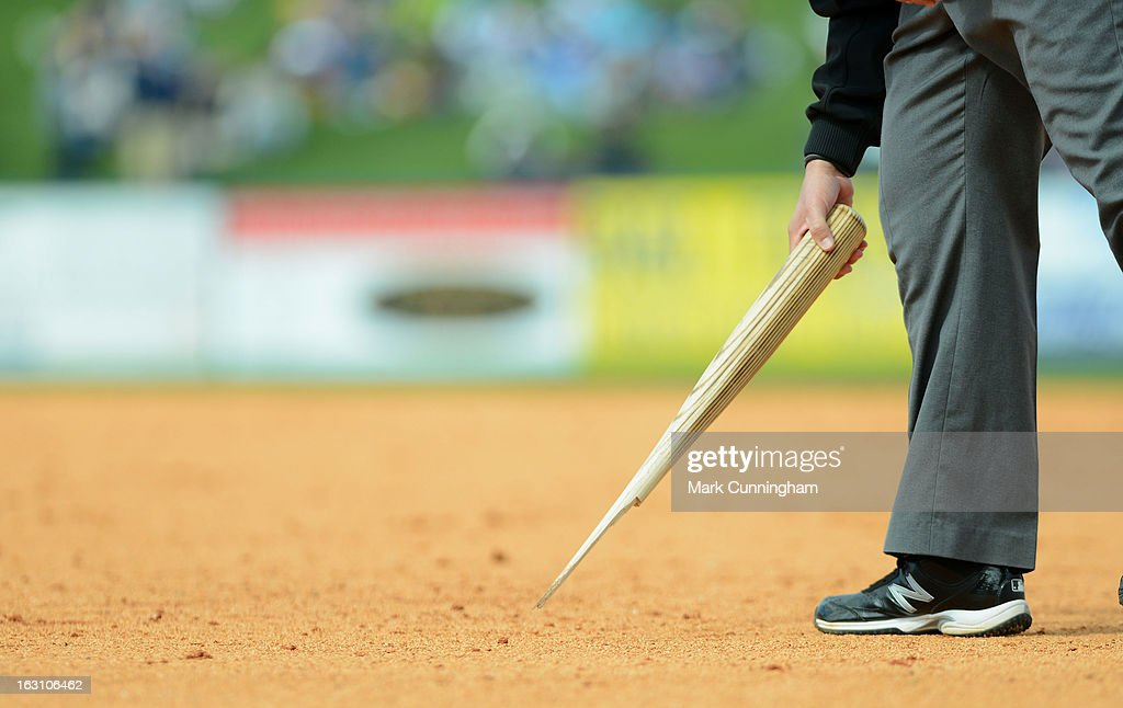 An umpire picks up a broken baseball bat from the field during the spring training game between the Detroit Tigers and the Pittsburgh Pirates at Joker Marchant Stadium on March 2, 2013 in Lakeland, Florida. The Tigers defeated the Pirates 4-1.