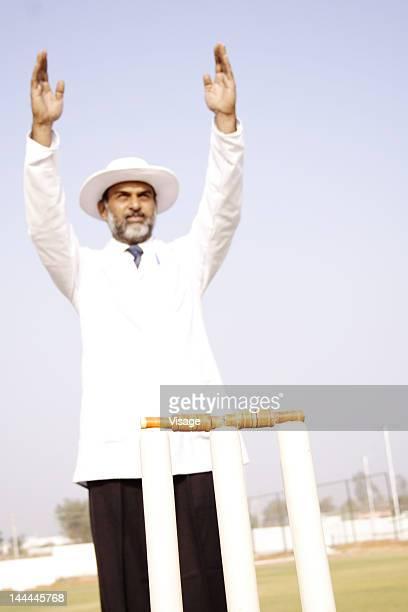 An umpire raising his hands