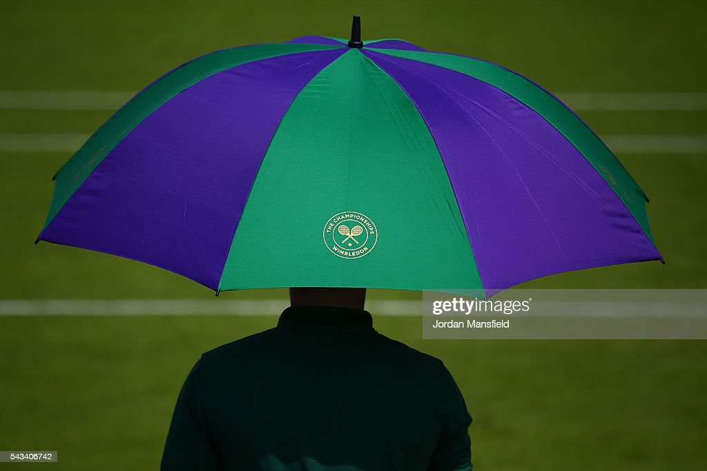 An umpire sits undernieth an umbrella on day two of the Wimbledon Lawn Tennis Championships at the All England Lawn Tennis and Croquet Club on June 28, 2016 in London, England.