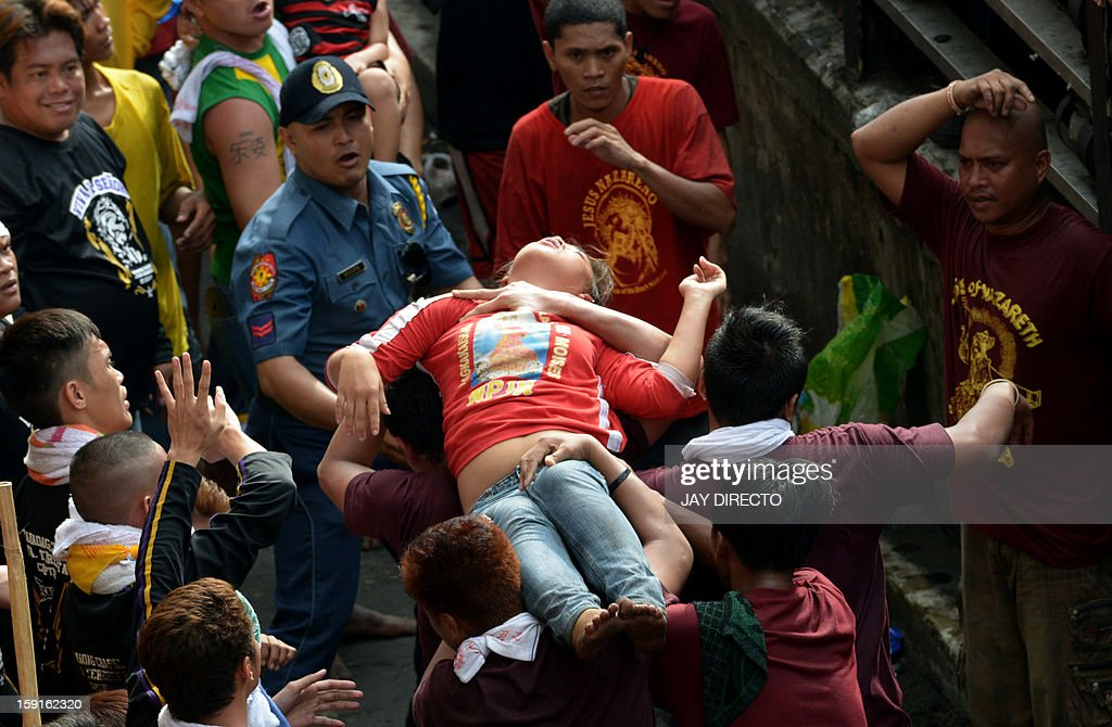 An unconscious devotee is carried to the nearest red cross in central Manila on January 9, 2013. Masses of Catholic devotees swept through the Philippine capital on Wednesday in a spectacular outpouring of passion for a centuries-old statue of Jesus Christ that many believe can perform miracles. In the nation's biggest annual religious festival, barefoot men and women crammed into Manila's streets hoping to touch the life-sized, black icon as it was paraded through the city's historic area for a day-long procession. AFP PHOTO / Jay DIRECTO