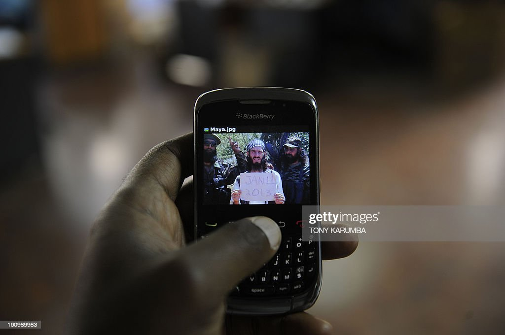 An undated photo of Abu Mansoor al-Amriki [C] aka 'the American' taken at an undisclosed location is seen on a mobile phone screen in Nairobi, Kenya on February 07, 2013. Once his reputation was of a feared fighter, an American born extremist who left small town Alabama to wage war alongside Al-Qaeda linked Somali Islamists and who called on other foreigners to join. Today, Omar Hamami -- better known as Abu Mansoor al-Amriki or 'the American' -- has split from the insurgents who want to kill him. He spends his days firing off insults of corruption and abuse at his former Shebab colleagues, even referring to himself as the 'former poster boy' of the group. AFP PHOTO/Tony KARUMBA