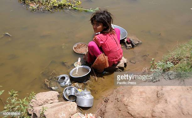An underprivileged Pakistani girl washes dishes from a pond of dirty water in the outskirts of Islamabad Poverty is not a new portentous in the...