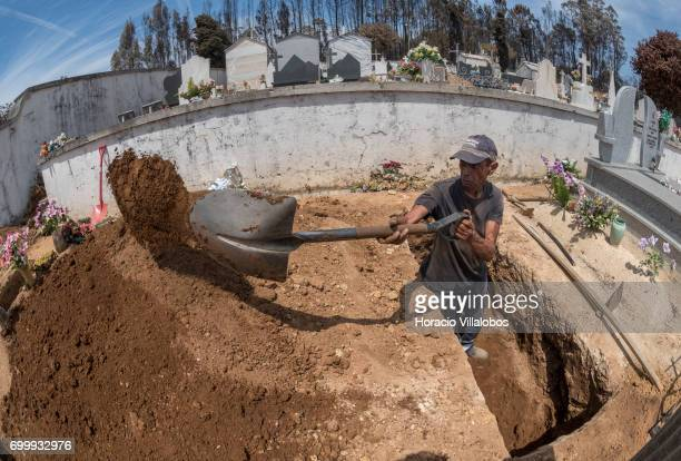 An undertaker digs one of the graves for the victims of the forest fire at the small village cemetery on June 22 2017 in Vila Facaia Portugal This...