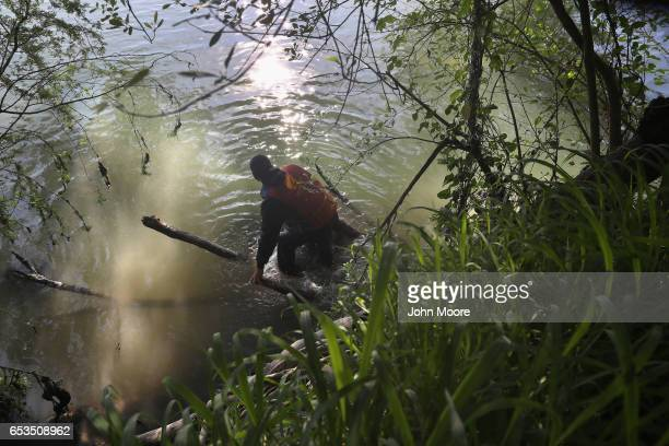 An undocumented immigrant wades across the Rio Grande at the USMexico border on March 14 2017 in Roma Texas US Border Patrol agents had intercepted...