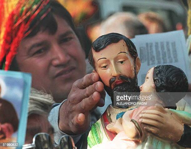 An unemployed Argentine touches the image of San Cayetanopatron saint of the workers and protector of the poor07 August as hundreds of thousands of...