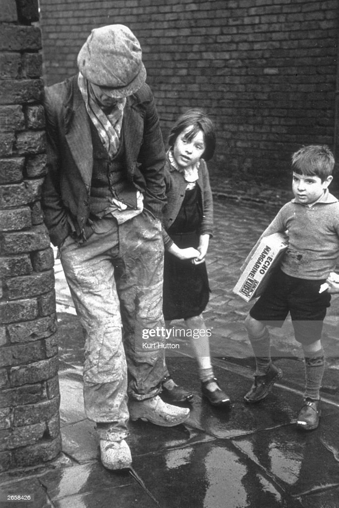 An unemployed man leaning against a wall in Wigan, with two children looking on. Original Publication: Picture Post - 228 - Wigan - pub. 1939