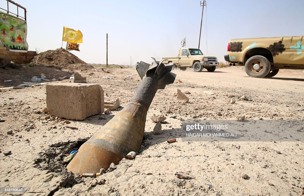 An unexploded mortar shell is seen half buried in the ground in Fallujah, 50 kilometres (30 miles) from the Iraqi capital Baghdad, after Iraqi forces retook the embattled city from the Islamic State group on June 26, 2016. Iraqi Prime Minister Haider al-Abadi urged all Iraqis to celebrate the recapture of Fallujah by the security forces and vowed the national flag would be raised in Mosul soon. While the battle has been won, Iraq still faces a major humanitarian crisis in its aftermath, with tens of thousands of people who fled the fighting desperately in need of assistance in the searing summer heat. ALI
