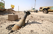TOPSHOT An unexploded mortar shell is seen half buried in the ground in Fallujah 50 kilometres from the Iraqi capital Baghdad after Iraqi forces...