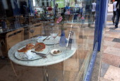 An unfinished pizza and a glass of wine are pictured on table beside the cracked shop front window of a restaurant in Clapham Junction in south...