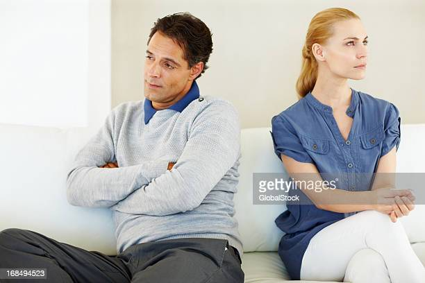 An unhappy couple sitting facing away with arms crossed