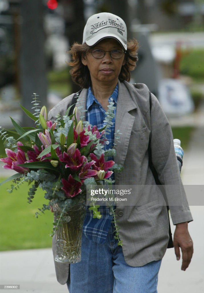 An unidenfitied fan carries a vase of flowers to the ...