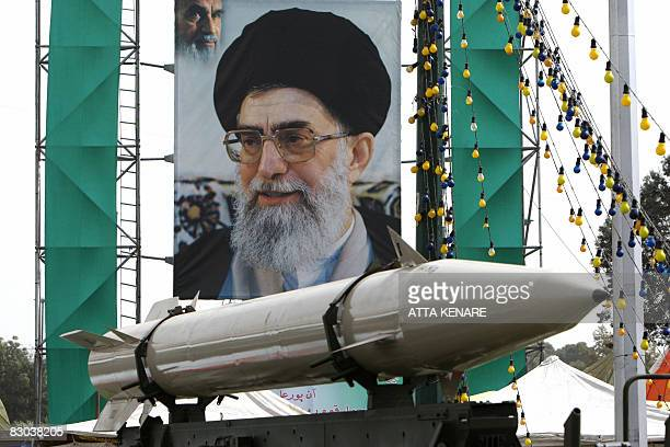 An unidentifed Iranian missile stands on display in front of a large portrait of Iran's Supreme Leader Ayatollah Ali Khamenei in a square in south...