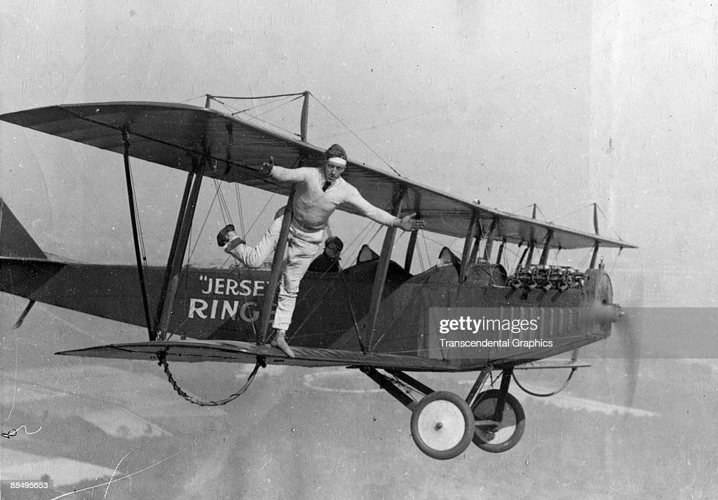 An unidentiffied 'barnstorming' pilot and a wingwalker perform stunts on a Curtiss 'Flying Jenny' biplane in the air above New Jersey, 1910s or 1920s.
