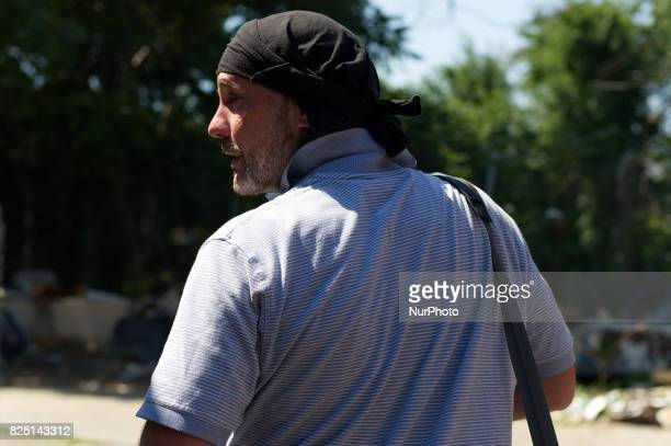 An unidentified 40 year old male addict looks over his shoulder as he walks near the heroin camp located alongside the Conrail train track in the...