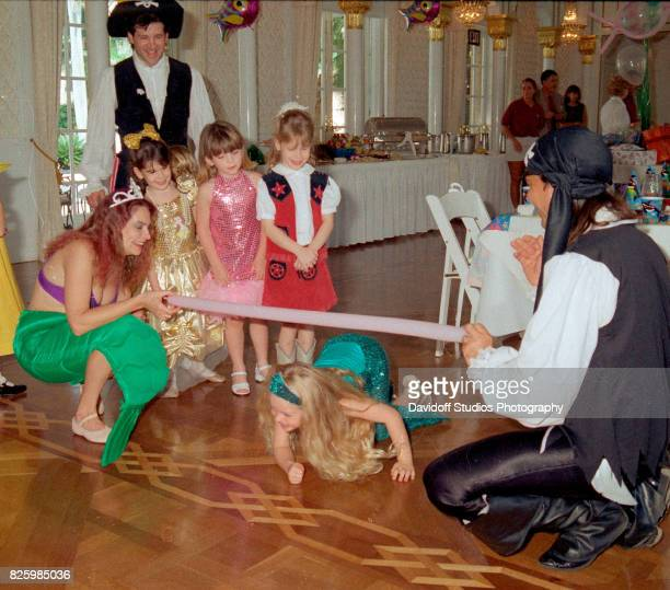 An unidentified actor dressed as a pirate stands with Tiffany Trump in a costume during the latter's fifth birthday party at the MaraLago estate Palm...
