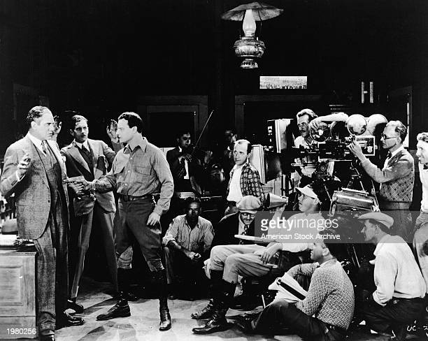 An unidentified actor holds another man at gunpoint as a director and film crew shoot a scene for an unidentified silent crime film 1920s