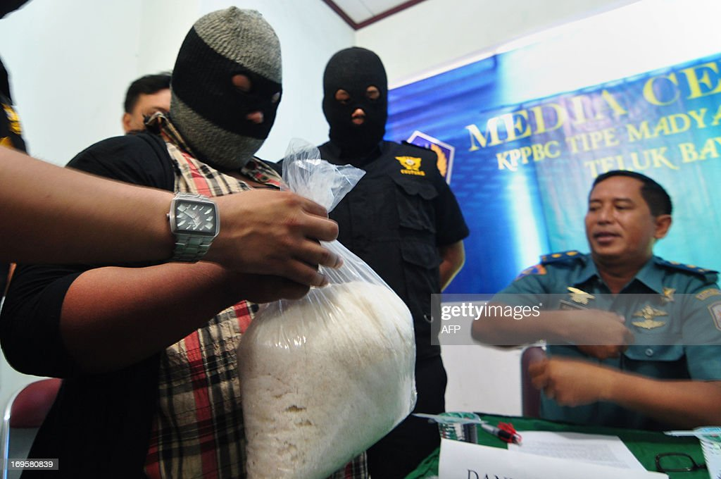 An unidentified arrested Indonesian woman and suspected illegal drugs courier (L) holds a bag containing 2.8 kilos (6.2 lbs) of 'crystal meth' (methamphetamine hydrochloride), locally known as 'shabu', worth 3.8 billion Indonesian rupiah (387,600 USD) at the customs office in Padang, West Sumatra province on May 28, 2013. According to authorities the drugs originated from the Philippines and were destined for Jakarta when the suspect was arrested at Padang airport on arrival from Malaysia. The drugs were hidden in the interior lining of luggage.