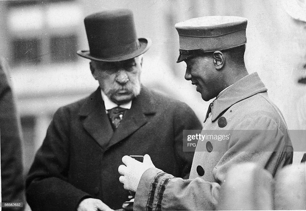 An unidentified bellboy smiles as he speaks with American financier John Pierpont Morgan Sr dressed in a coat and top hat early 1900s
