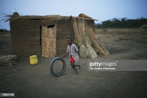 An unidentified boy plays with a tire outside the family house on August 21 2006 in Mphandula village about 30 miles outside Lilongwe Malawi Its one...