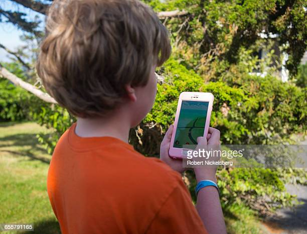 An unidentified boy searches his handset during a search with the Pokémon Go application in East Orleans Massachusetts on July 10 2016
