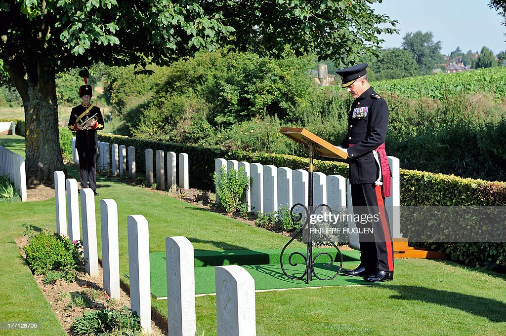 An unidentified British army officer delivers a speech on August 21, 2013 during the burial of an unknown soldier at the Fifteen Ravine British Cemetery in Villers-Plouich, northern France. 'Fifteen Ravine' was the name given by the Army to the shallow ravine, once bordered by fifteen trees, which ran at right angles to the railway about 800 metres south of the village of Villers-Plouich. The cemetery, sometimes called Farm Ravine Cemetery, was begun by the 17th Welsh Regiment in April 1917, a few days after the capture of the ravine by the 12th South Wales Borderers. It continued in use during the Battle of Cambrai (November 1917) and until March 1918, when the ravine formed the boundary between the Third and Fifth Armies. On 22 March, the second day of the great German offensive, the ground passed into their hands after severe fighting, and it was not regained until the end of the following September. In March 1918, the cemetery contained 107 graves (now Plot I), but it was greatly enlarged after the Armistice when graves were brought in from the battlefields south-west of Cambrai and other cemeteries.