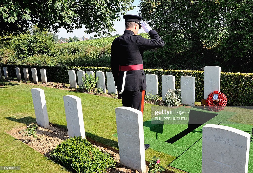 An unidentified British army officer pays his respect on August 21, 2013 during the burial of an unknown soldier at the Fifteen Ravine British Cemetery in Villers-Plouich, northern France. 'Fifteen Ravine' was the name given by the Army to the shallow ravine, once bordered by fifteen trees, which ran at right angles to the railway about 800 metres south of the village of Villers-Plouich. The cemetery, sometimes called Farm Ravine Cemetery, was begun by the 17th Welsh Regiment in April 1917, a few days after the capture of the ravine by the 12th South Wales Borderers. It continued in use during the Battle of Cambrai (November 1917) and until March 1918, when the ravine formed the boundary between the Third and Fifth Armies. On 22 March, the second day of the great German offensive, the ground passed into their hands after severe fighting, and it was not regained until the end of the following September. In March 1918, the cemetery contained 107 graves (now Plot I), but it was greatly enlarged after the Armistice when graves were brought in from the battlefields south-west of Cambrai and other cemeteries.