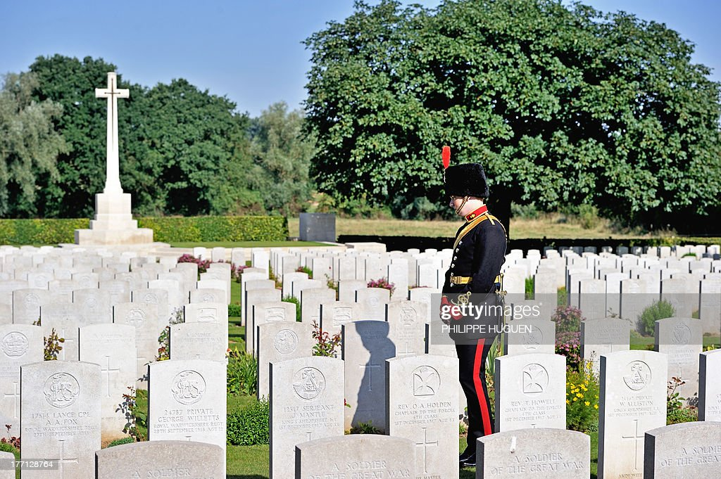An unidentified British army soldier pays his respect on August 21, 2013 after the burial of an unknown soldier at the Fifteen Ravine British Cemetery in Villers-Plouich, northern France. 'Fifteen Ravine' was the name given by the Army to the shallow ravine, once bordered by fifteen trees, which ran at right angles to the railway about 800 metres south of the village of Villers-Plouich. The cemetery, sometimes called Farm Ravine Cemetery, was begun by the 17th Welsh Regiment in April 1917, a few days after the capture of the ravine by the 12th South Wales Borderers. It continued in use during the Battle of Cambrai (November 1917) and until March 1918, when the ravine formed the boundary between the Third and Fifth Armies. On 22 March, the second day of the great German offensive, the ground passed into their hands after severe fighting, and it was not regained until the end of the following September. In March 1918, the cemetery contained 107 graves (now Plot I), but it was greatly enlarged after the Armistice when graves were brought in from the battlefields south-west of Cambrai and other cemeteries. AFP PHOTO / PHILIPPE HUGUEN