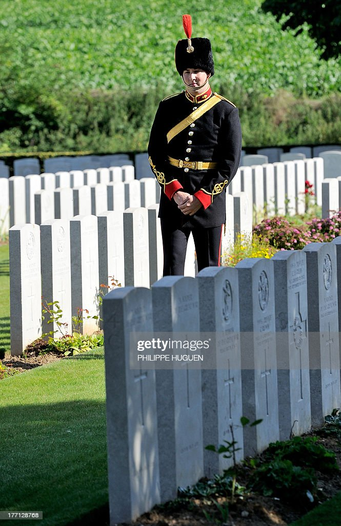 An unidentified British army soldier pays his respect on August 21, 2013 after the burial of an unknown soldier at the Fifteen Ravine British Cemetery in Villers-Plouich, northern France. 'Fifteen Ravine' was the name given by the Army to the shallow ravine, once bordered by fifteen trees, which ran at right angles to the railway about 800 metres south of the village of Villers-Plouich. The cemetery, sometimes called Farm Ravine Cemetery, was begun by the 17th Welsh Regiment in April 1917, a few days after the capture of the ravine by the 12th South Wales Borderers. It continued in use during the Battle of Cambrai (November 1917) and until March 1918, when the ravine formed the boundary between the Third and Fifth Armies. On 22 March, the second day of the great German offensive, the ground passed into their hands after severe fighting, and it was not regained until the end of the following September. In March 1918, the cemetery contained 107 graves (now Plot I), but it was greatly enlarged after the Armistice when graves were brought in from the battlefields south-west of Cambrai and other cemeteries.