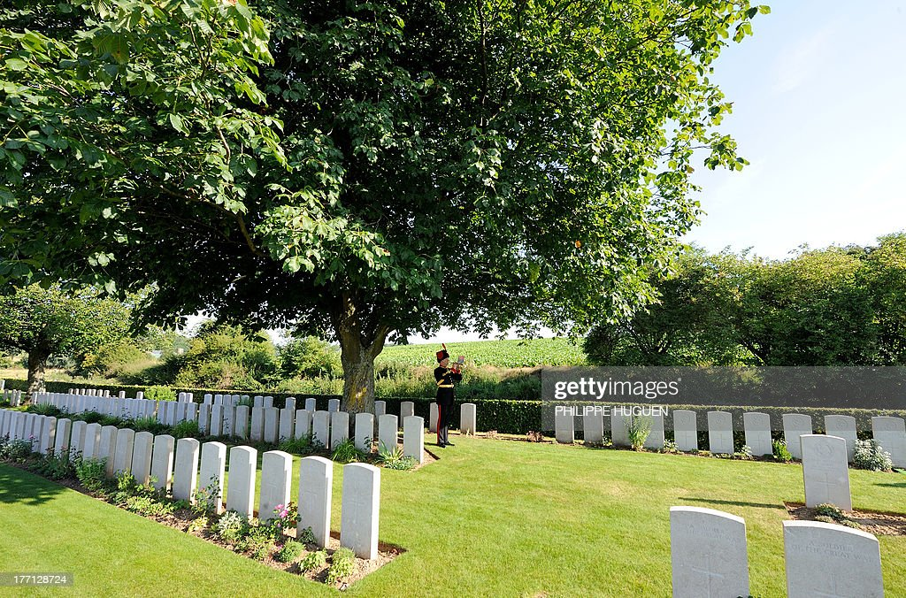 An unidentified British army soldier performs the last post on August 21, 2013 during the burial of an unknown soldier at the Fifteen Ravine British Cemetery in Villers-Plouich, northern France. 'Fifteen Ravine' was the name given by the Army to the shallow ravine, once bordered by fifteen trees, which ran at right angles to the railway about 800 metres south of the village of Villers-Plouich. The cemetery, sometimes called Farm Ravine Cemetery, was begun by the 17th Welsh Regiment in April 1917, a few days after the capture of the ravine by the 12th South Wales Borderers. It continued in use during the Battle of Cambrai (November 1917) and until March 1918, when the ravine formed the boundary between the Third and Fifth Armies. On 22 March, the second day of the great German offensive, the ground passed into their hands after severe fighting, and it was not regained until the end of the following September. In March 1918, the cemetery contained 107 graves (now Plot I), but it was greatly enlarged after the Armistice when graves were brought in from the battlefields south-west of Cambrai and other cemeteries.