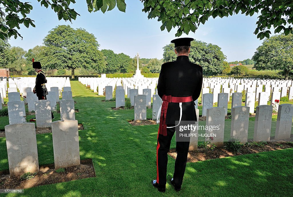 An unidentified British army soldiers pay their respect on August 21, 2013 after the burial of an unknown soldier at the Fifteen Ravine British Cemetery in Villers-Plouich, northern France. 'Fifteen Ravine' was the name given by the Army to the shallow ravine, once bordered by fifteen trees, which ran at right angles to the railway about 800 metres south of the village of Villers-Plouich. The cemetery, sometimes called Farm Ravine Cemetery, was begun by the 17th Welsh Regiment in April 1917, a few days after the capture of the ravine by the 12th South Wales Borderers. It continued in use during the Battle of Cambrai (November 1917) and until March 1918, when the ravine formed the boundary between the Third and Fifth Armies. On 22 March, the second day of the great German offensive, the ground passed into their hands after severe fighting, and it was not regained until the end of the following September. In March 1918, the cemetery contained 107 graves (now Plot I), but it was greatly enlarged after the Armistice when graves were brought in from the battlefields south-west of Cambrai and other cemeteries.