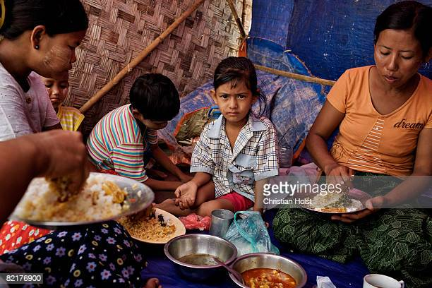An unidentified Burmese family eating in a makeshift shelter on the side of a road in the township of South Okkalapa May 16 2008 in the Northern part...