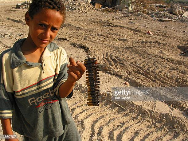 An unidentified child from the Jenin refugee camp holds up the left over rounds fired this morning allegedly by an Israeli armored personnel carrier...