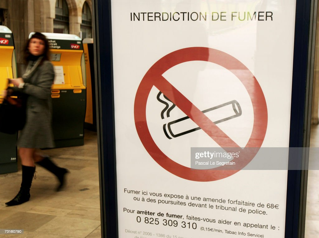 An unidentified commuter walks past an interdiction smoknig sign inside the Eastern railway station on January 31, 2007 in Paris, France.France introduce smoking ban in public places from February 1, 2007. Bars, restaurants, hotels and night clubs will follow from January 1, 2008.